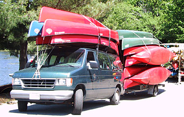 Our van and trailer fully loaded with canoes for delivery.
