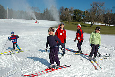 Kids skiing in front of snow guns at Weston Ski Track.