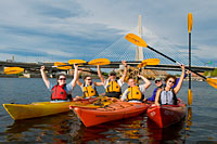 Unforgettable Group and Corporate Outings at Charles River Canoe & Kayak. Here, a happy crowd relaxes in the shadow of Boston's Zakim Bridge during a skyline outing.