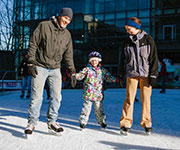 Parents skate with their young daughter.