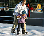 A skating instructor helps a young girl skate for the first time.