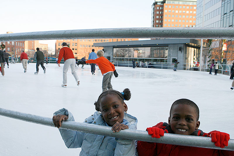 Two young kids on the skating rink.