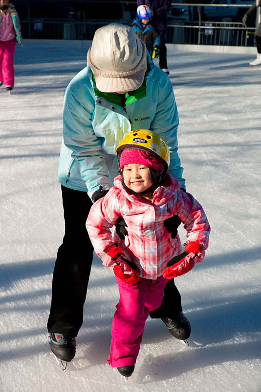Mother helping her young daughter skate.