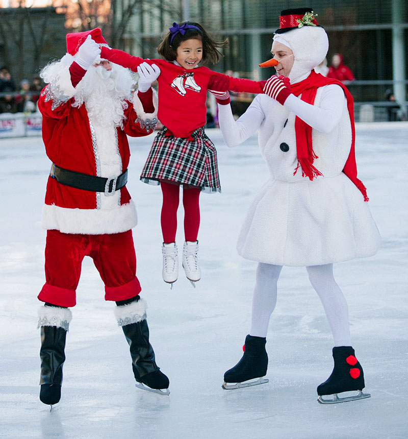 Costumed skaters Santa and Frosty hold up a young skating girl.