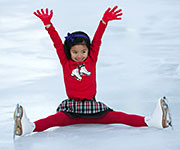 A young figure skater acknowledges the crowd after her performance.