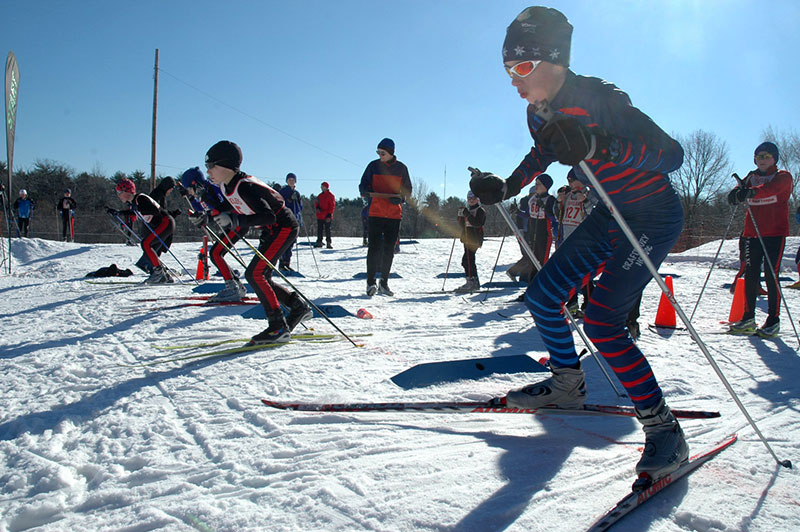 Kids lined up at the starting line begin a ski race.