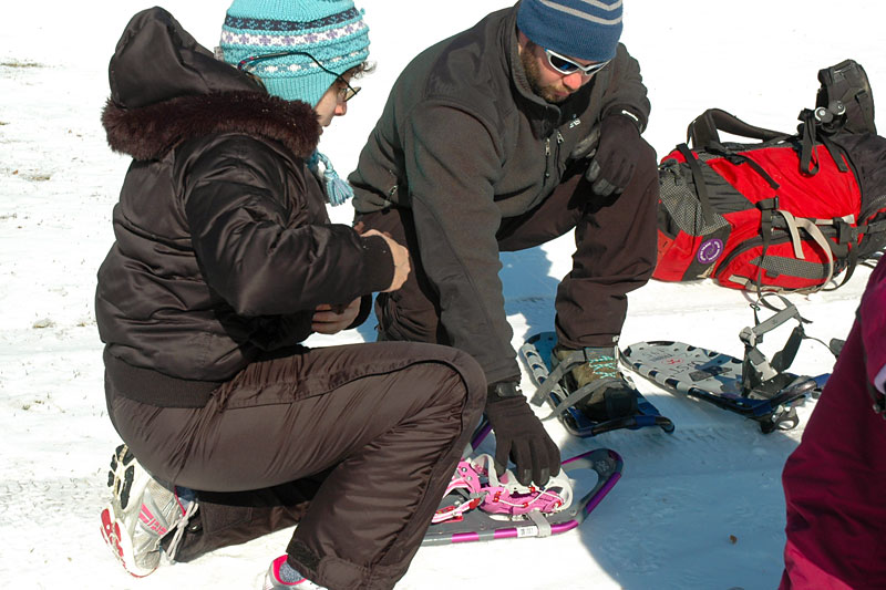 Our snowshoe instructor helps a student put on her snowshoes.