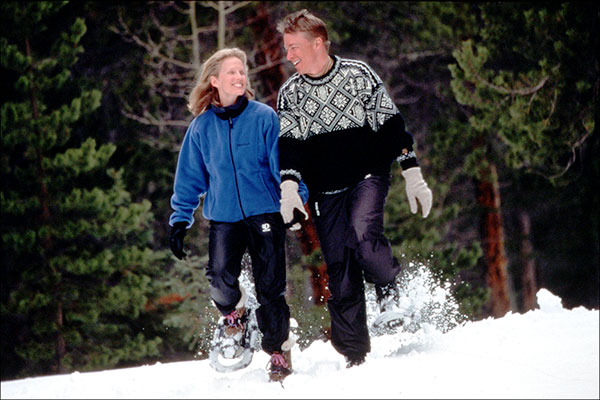 A couple snowshoeing and holding hands.