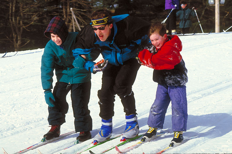 Two kids ski down a hill with smiles on their faces.